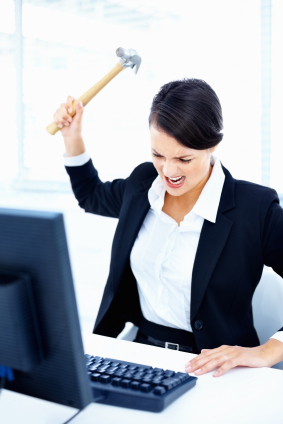 Angry business lady hitting a computer keyboard with a hammer