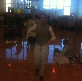 Teen girl in fencing uniform