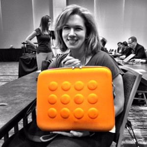 "Tricia McKnight totes a geo-circle brief case in ""It"" color orange."