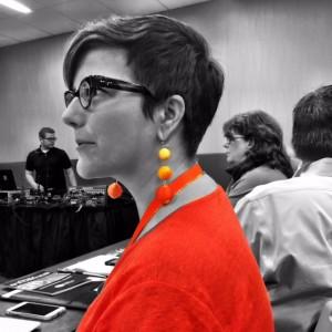 Amy Higgins adds edge with gradient orange drop earrings.